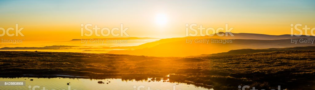 Golden sunrise over misty mountains panorama Brecon Beacons NP Wales stock photo