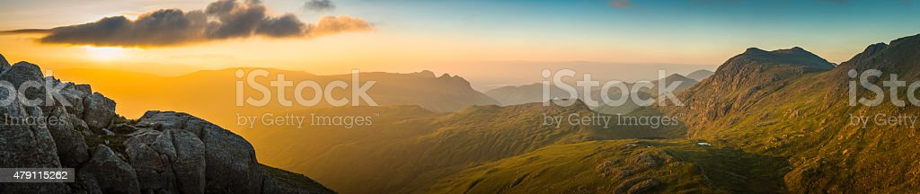 Golden sunrise over mountain peaks panorama Langdale Pikes Lake District stock photo