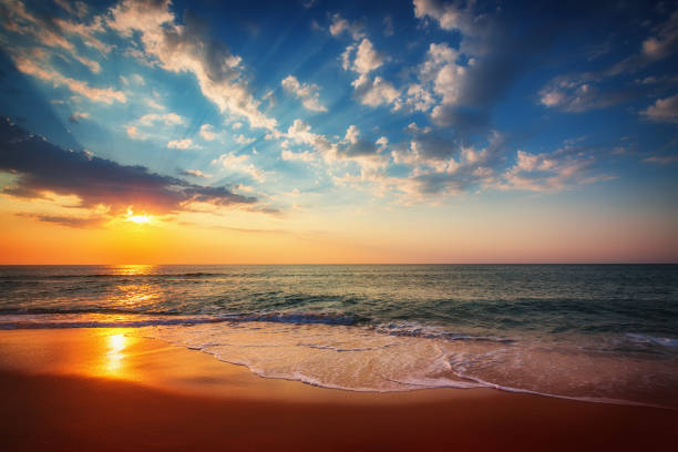 Golden sunrise over tropical beach Beautiful cloudscape over the sea, sunrise shot sunset stock pictures, royalty-free photos & images