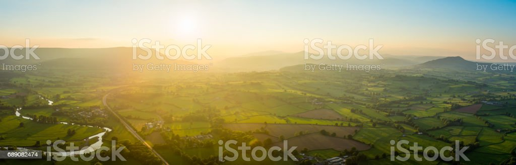 Golden sunset aerial panorama over idyllic green summer countryside mountains stock photo