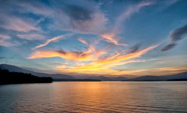 Golden Sunset at the Ashokan Reservoir in New York. Dramatic Sunset with Blue Sky at the Ashokan Reservoir in Ulster County in New York. Golden light reflects on the Mountains and calm reservoir surface. catskill mountains stock pictures, royalty-free photos & images