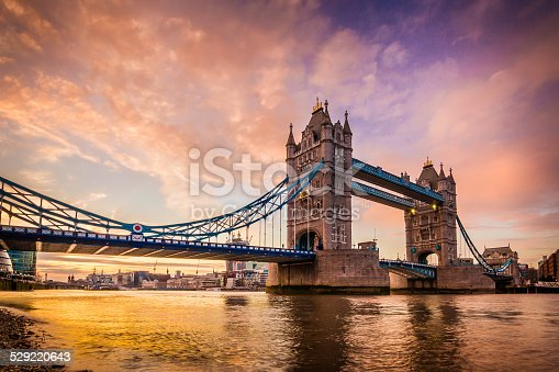 A vivid and spectacular golden sunset on the river Thames Southbank overlooking the iconic landmark and famous tourist attraction Tower Bridge in the capital city of London, United Kingdom. Shot with Canon EOS 60D, ISO 100, boosted saturation to emphasize colors, slight vignette added