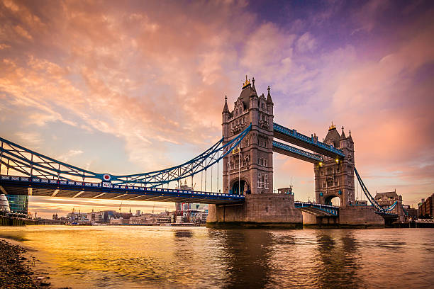 Golden sunset at Tower Bridge's Southbank in city of London A vivid and spectacular golden sunset on the river Thames Southbank overlooking the iconic landmark and famous tourist attraction Tower Bridge in the capital city of London, United Kingdom. Shot with Canon EOS 60D, ISO 100, boosted saturation to emphasize colors, slight vignette added bascule bridge stock pictures, royalty-free photos & images