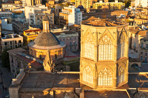 Golden sunset light illuminating Valencia Cathedral tower aerial cityscape Spain