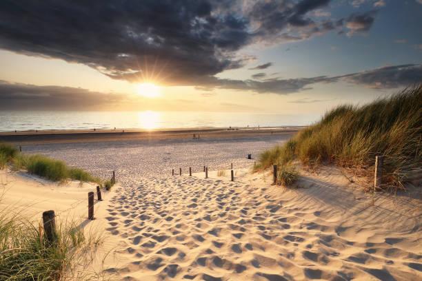gouden zonsondergang licht over zandpad naar Noordzeestrand tussen duinen foto