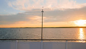 View on riverside from bow of moving cruise ship - golden sunset on the river