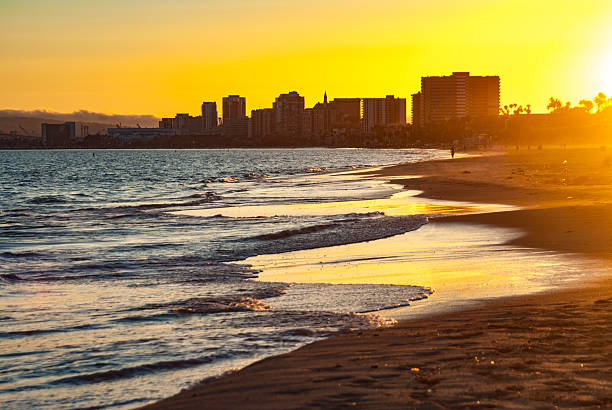 golden sunset over Long Beach Skyline yellow sky at twilight giving a golden glow to the surf in Long Beach, CA long beach california stock pictures, royalty-free photos & images