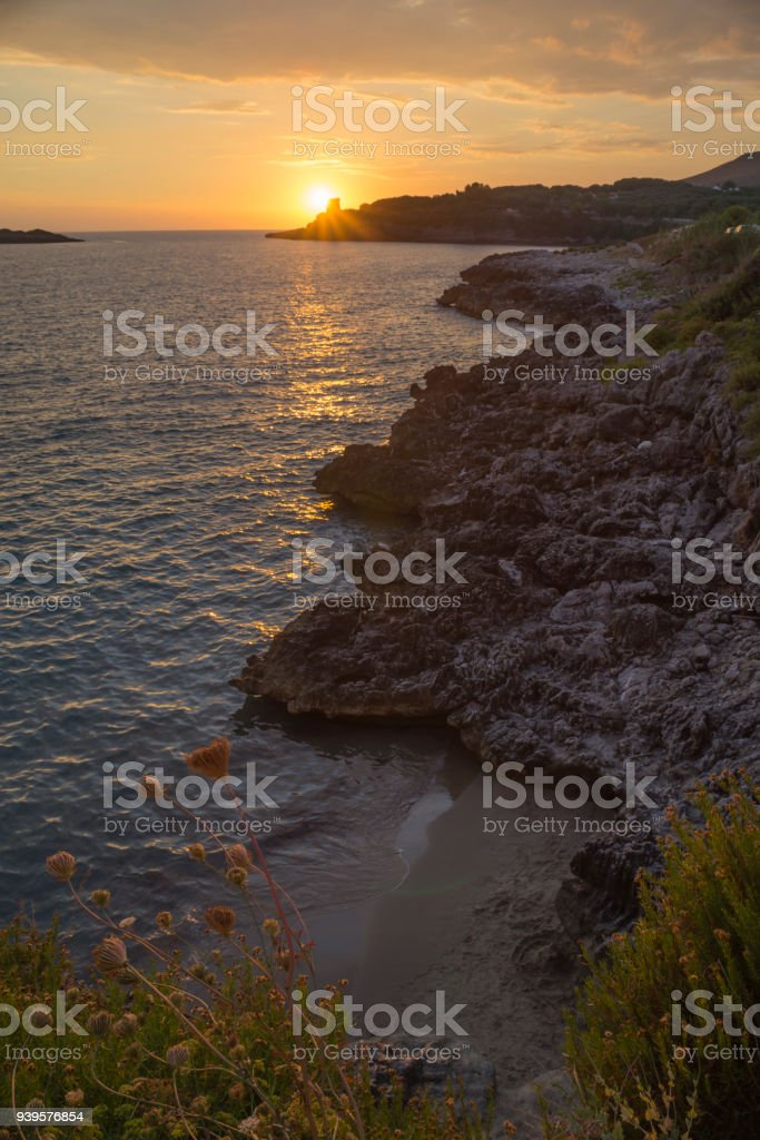Golden sunset over the Mediterranean Sea and the rocky coast at the city center of Marina di Camerota, Cilento, Campania, Italy stock photo