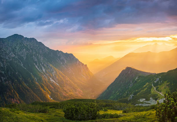 Golden sunset with sunbeams in big mountain landscape stock photo