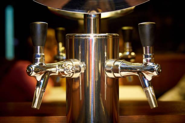 goldene wasserhähne für die abfüllung von bier mit einem unscharfen hintergrund-nahaufnahme - goldene bar stock-fotos und bilder