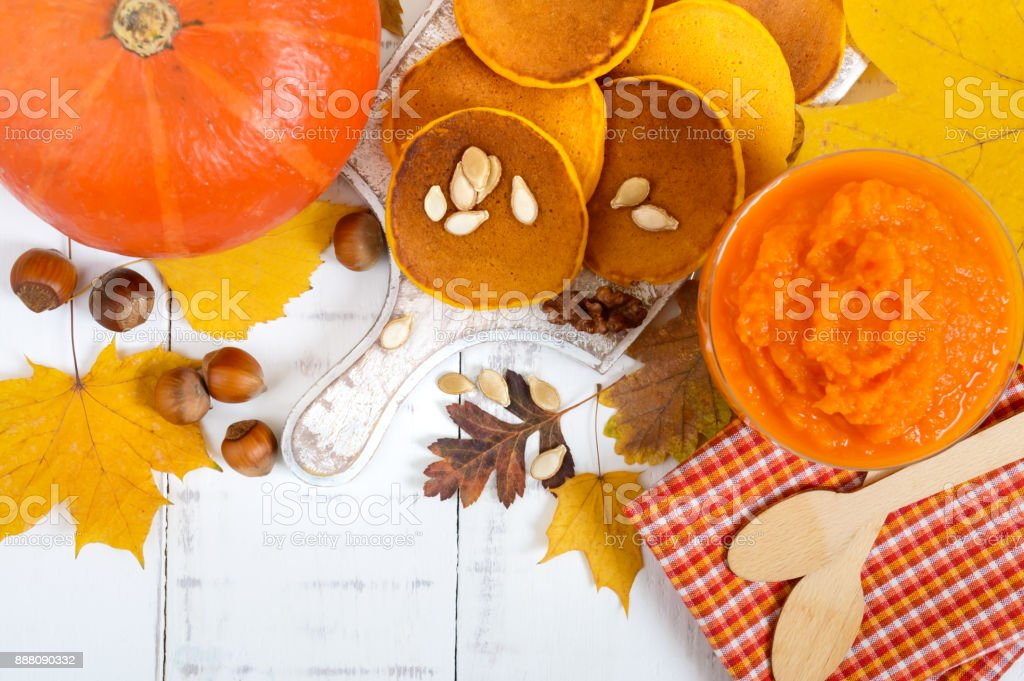 Golden tasty useful pumpkin pancakes, puree of a pumpkin on a white background. Autumn collection. stock photo