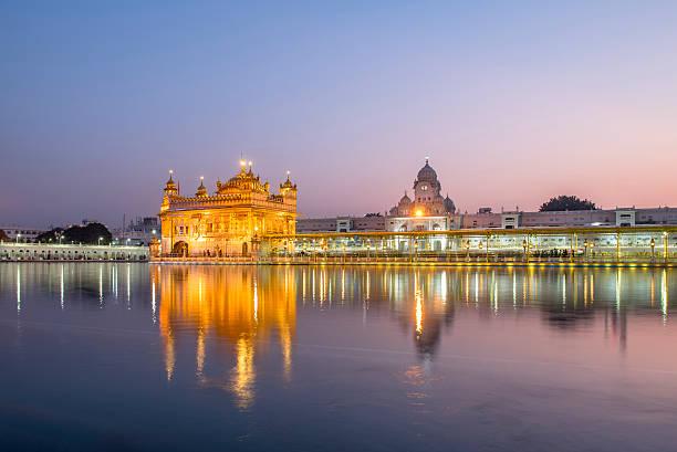 golden temple against pinky sky in amritsar, india - goldener tempel stock-fotos und bilder