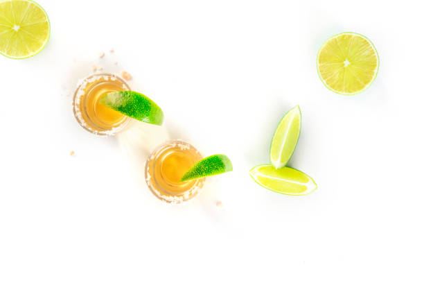 Golden tequila with lime slices on white, top shot stock photo