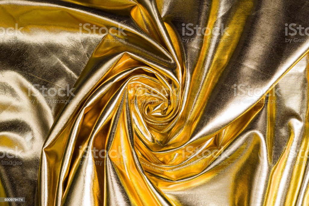 golden texture satin, twisted into spiral background stock photo