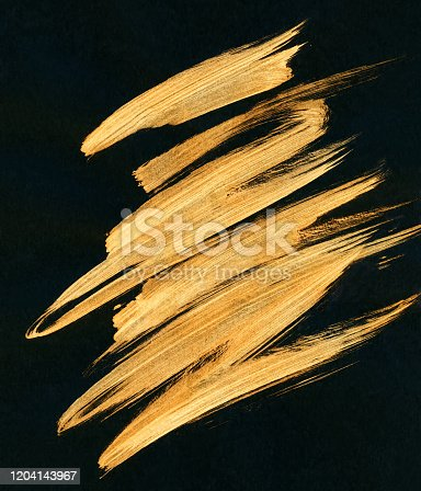 Golden traces of paint brush on black paper. Web banner.