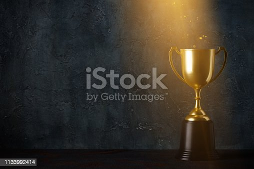 istock Golden trophy cup on dark table with rays of light 1133992414
