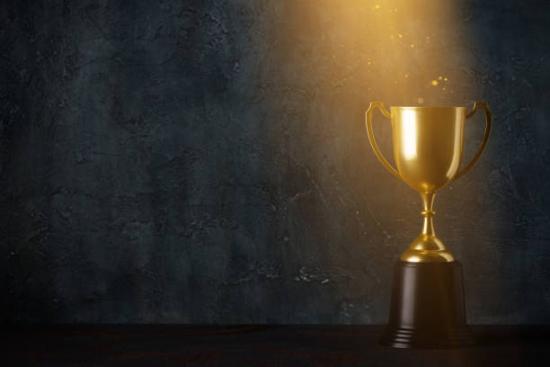 Golden trophy cup on dark table with rays of light Golden trophy cup on dark table with rays of light and glitter dust dark background with copy space trophy award stock pictures, royalty-free photos & images