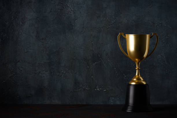 Golden trophy cup on table dark background