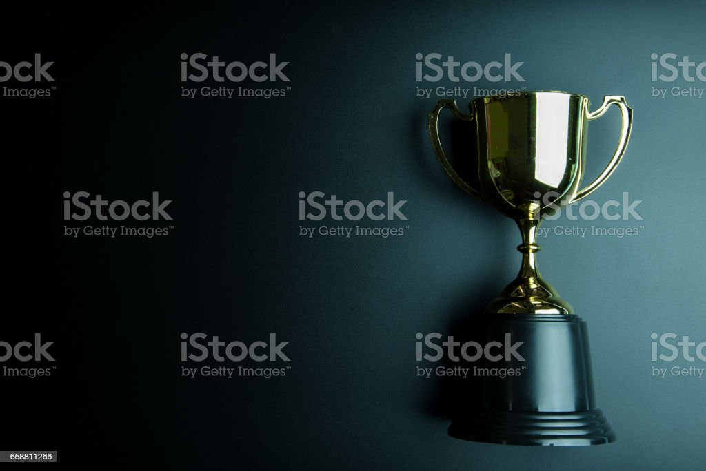 Golden trophy isolated on black background with copy space.Concept winner. stock photo