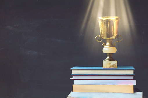 istock Golden trophy on pile of books, against blackboard, with sun rays over trophy; learning/achievement concept 908745612