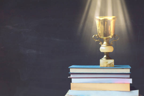 Golden trophy on pile of books, against blackboard, with sun rays over trophy; learning/achievement concept stock photo