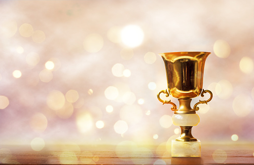 istock Golden trophy on wooden table, bokeh and glitter background with copy space 908738874