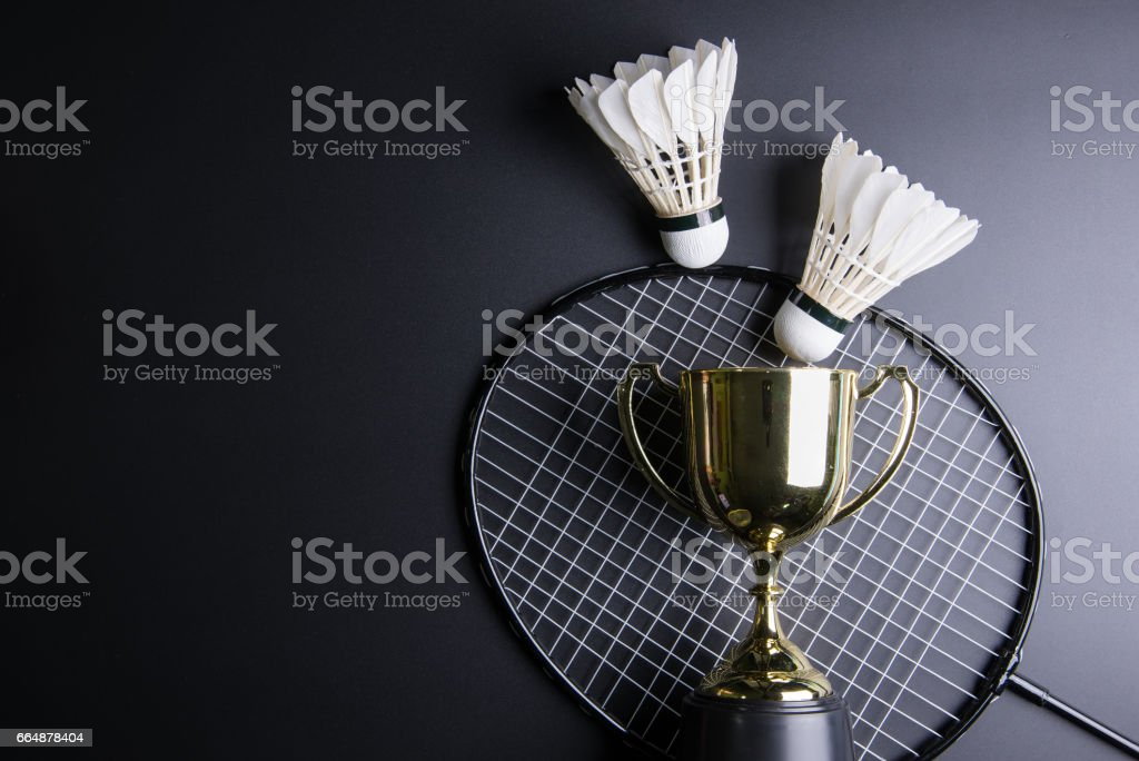 Golden trophy, Shuttlecocks and badminton racket on black background.Sport concept, Concept winner, Copy space image for your text. stock photo