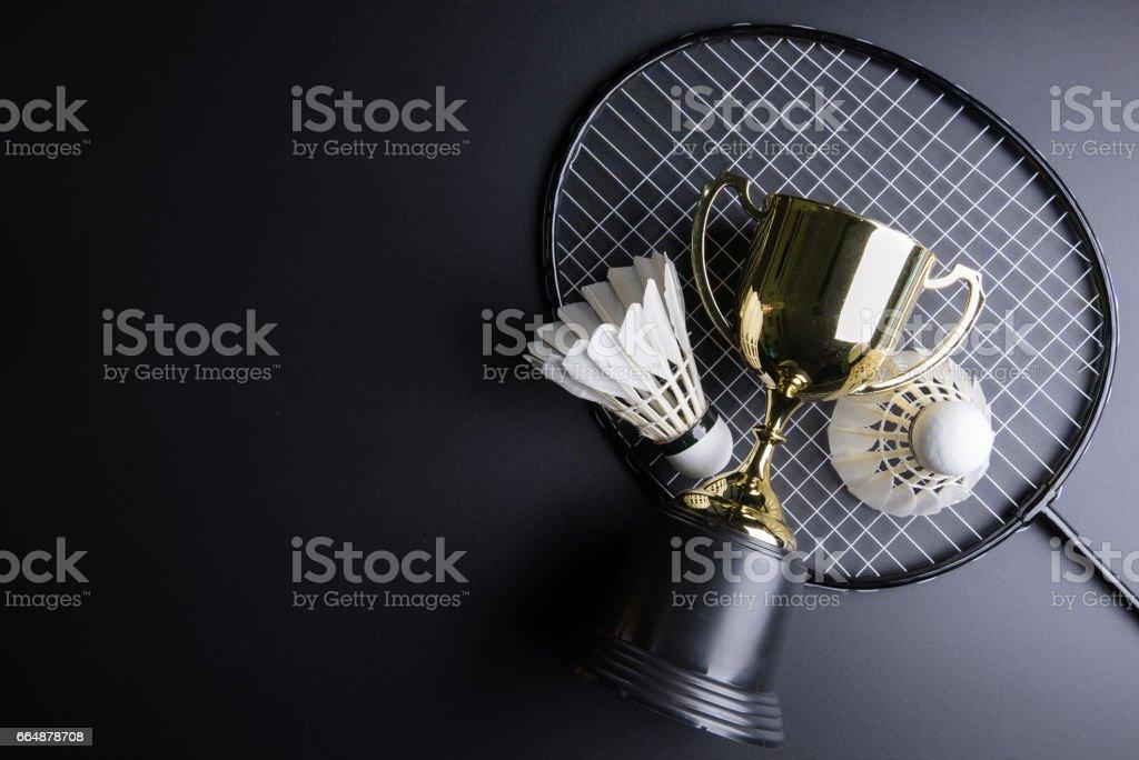Oro trofeo y Volantes badminton raqueta sobre fondo negro. Concepto de deporte, concepto ganador, imagen de espacio de copia de su texto. - foto de stock