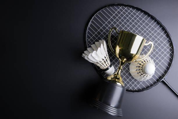 Goldene Trophäe, Federball und Badminton Schläger auf schwarzem Hintergrund. Sport-Konzept, Konzept-Gewinner, Raum-Bild für Ihren Text kopieren. – Foto