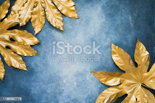 istock Golden tropical leaves on blue backdrop. Minimal summer exotic concept with copy space. Copy space, top view 1166582779