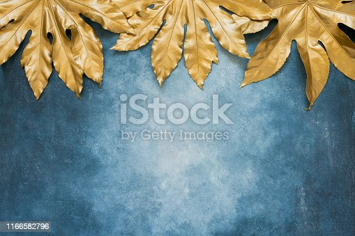 istock Golden tropical leaves on blue backdrop. Minimal summer exotic concept with copy space. Copy space, top view 1166582796