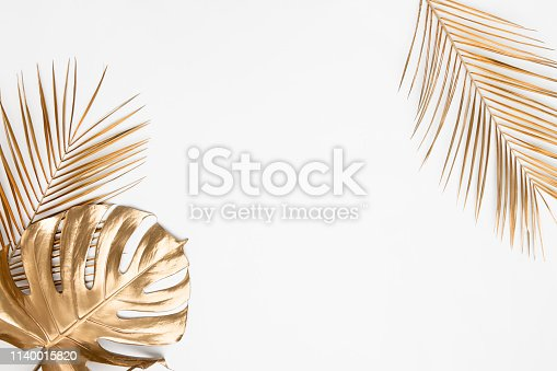 Golden painted tropical date palm and monstera leaves on plain white background isolated. Creative botanical layout border frame. Chic wedding invitation card mockup. Empty space, room for text.