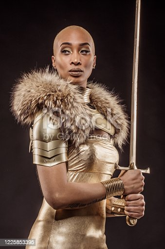 Golden viking inspired black warrior female in studio shot