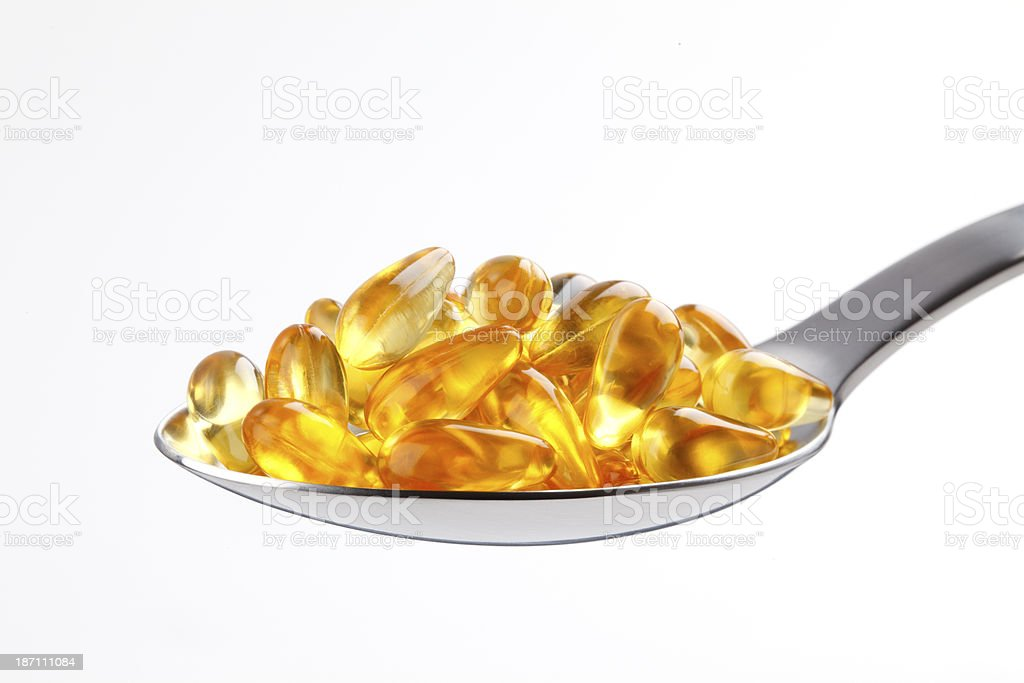 Golden vitamin capsules on a spoon royalty-free stock photo