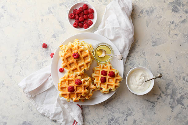 golden waffles with berry and honey stock photo