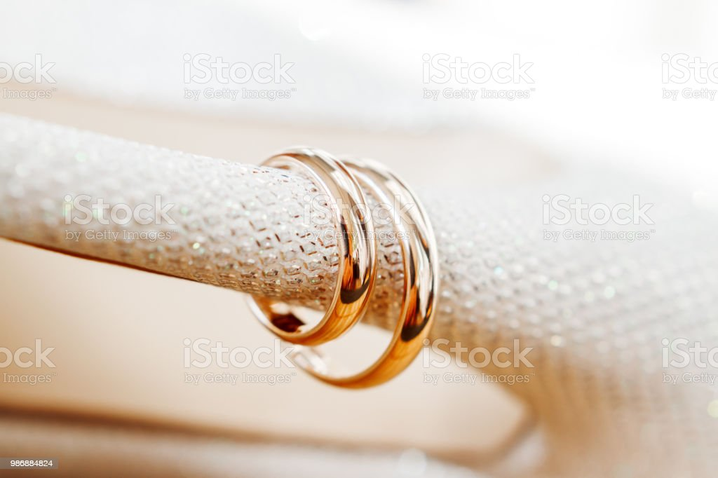 Golden wedding rings on bride shoes with rhinestones. Wedding jewelry details. Symbol of love and marriage. stock photo