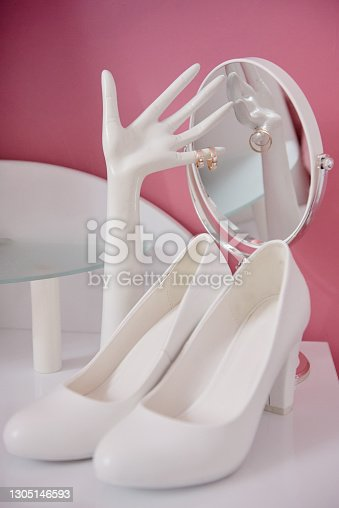 istock Golden wedding rings on ceramic hand-shaped jewelry holder, white bride's shoes and mirror on table, copy space. Wedding morning preparation. Bridal accessories, closeup. Marriage concept 1305146593