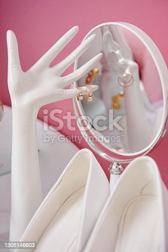 istock Golden wedding rings on ceramic hand-shaped jewelry holder, white bride's shoes and mirror on table, copy space. Wedding morning preparation. Bridal accessories, closeup. Marriage concept 1305146603
