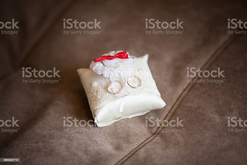 Golden wedding rings on decorated little white pillow. Marriage concept royaltyfri bildbanksbilder