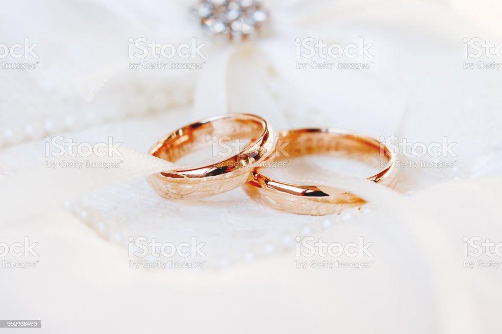 Anéis de casamento ouro sobre fundo branco de seda. Detalhes do casamento.  Símbolo de 1e19db02ddb02
