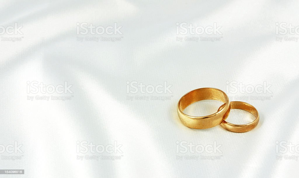 Golden wedding rings on white silk royalty-free stock photo