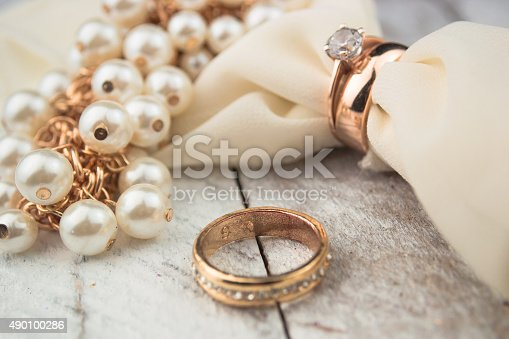 istock Golden wedding rings on white wood background 490100286