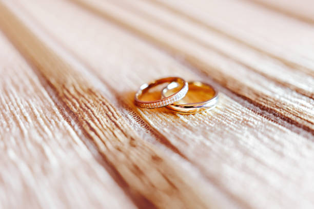 Golden wedding rings with diamonds on beige fabric background. Wedding details, symbol of love and marriage. stock photo