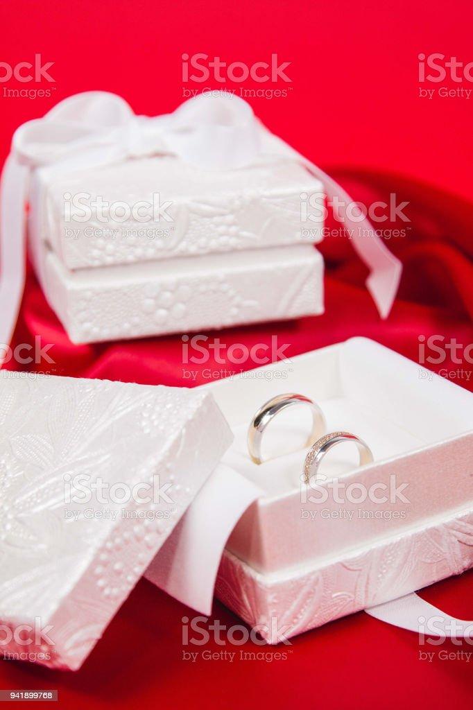 308c40b91f76 Anillos de boda oro con caja de lujo blanco sobre un fondo de seda foto de