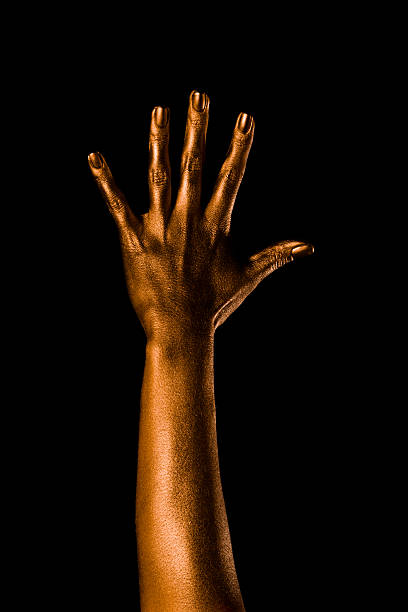 Golden woman's hand, five Close-up shot of woman's hand. Model was painted to create an image of Jil Masterson from Goldfinger (3rd film of James Bond series) body paint stock pictures, royalty-free photos & images
