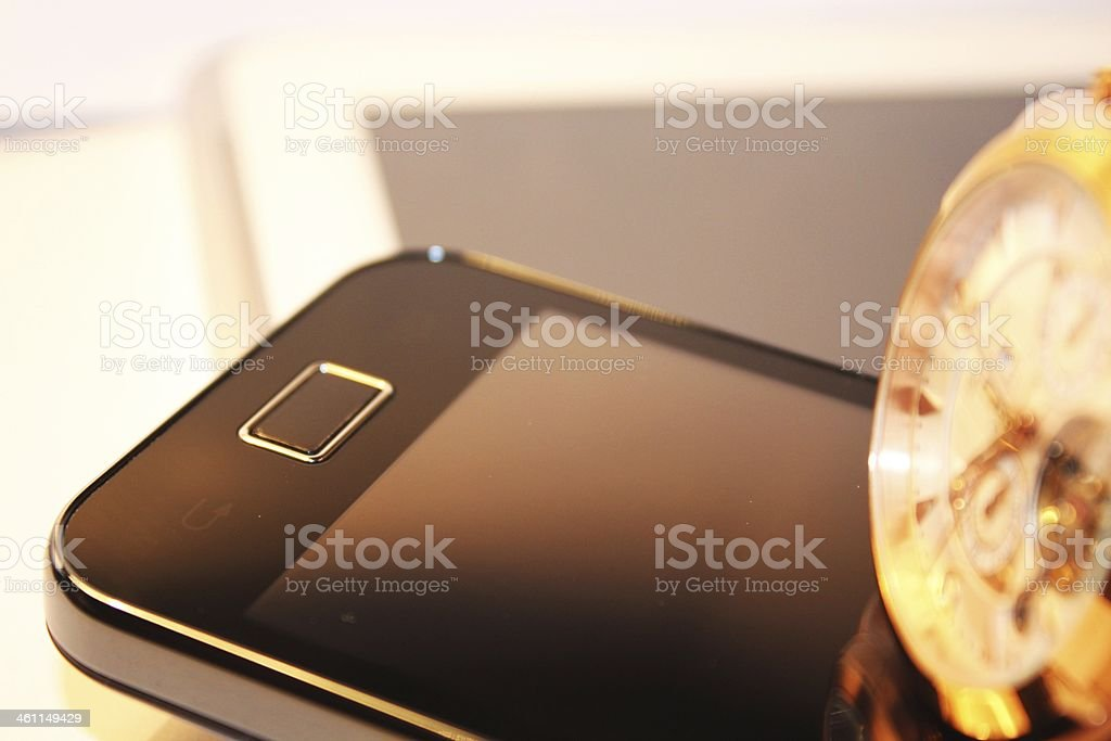 Golden wrist watch,smartphone and white tablet PC royalty-free stock photo