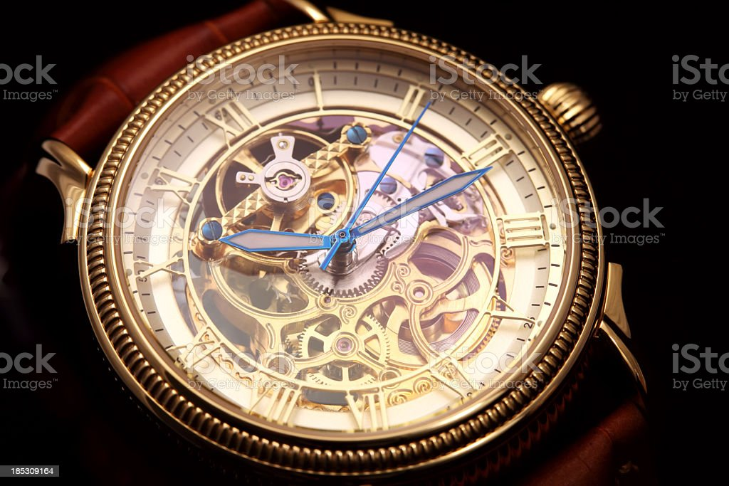 Golden wristwatch on black stock photo