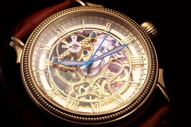 Golden wristwatch on black Golden wristwatch with a visible clockwork on black background. luxury watch stock pictures, royalty-free photos & images