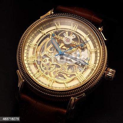 istock Golden wristwatch on black 483718275