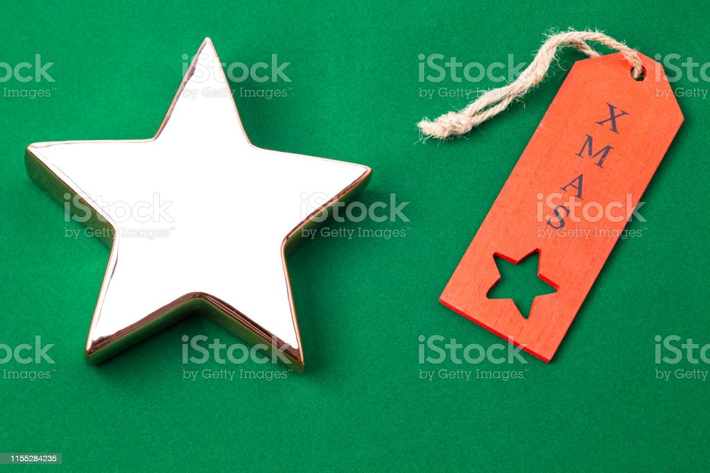 Image shows an golden x-mas star with red label isolated on green